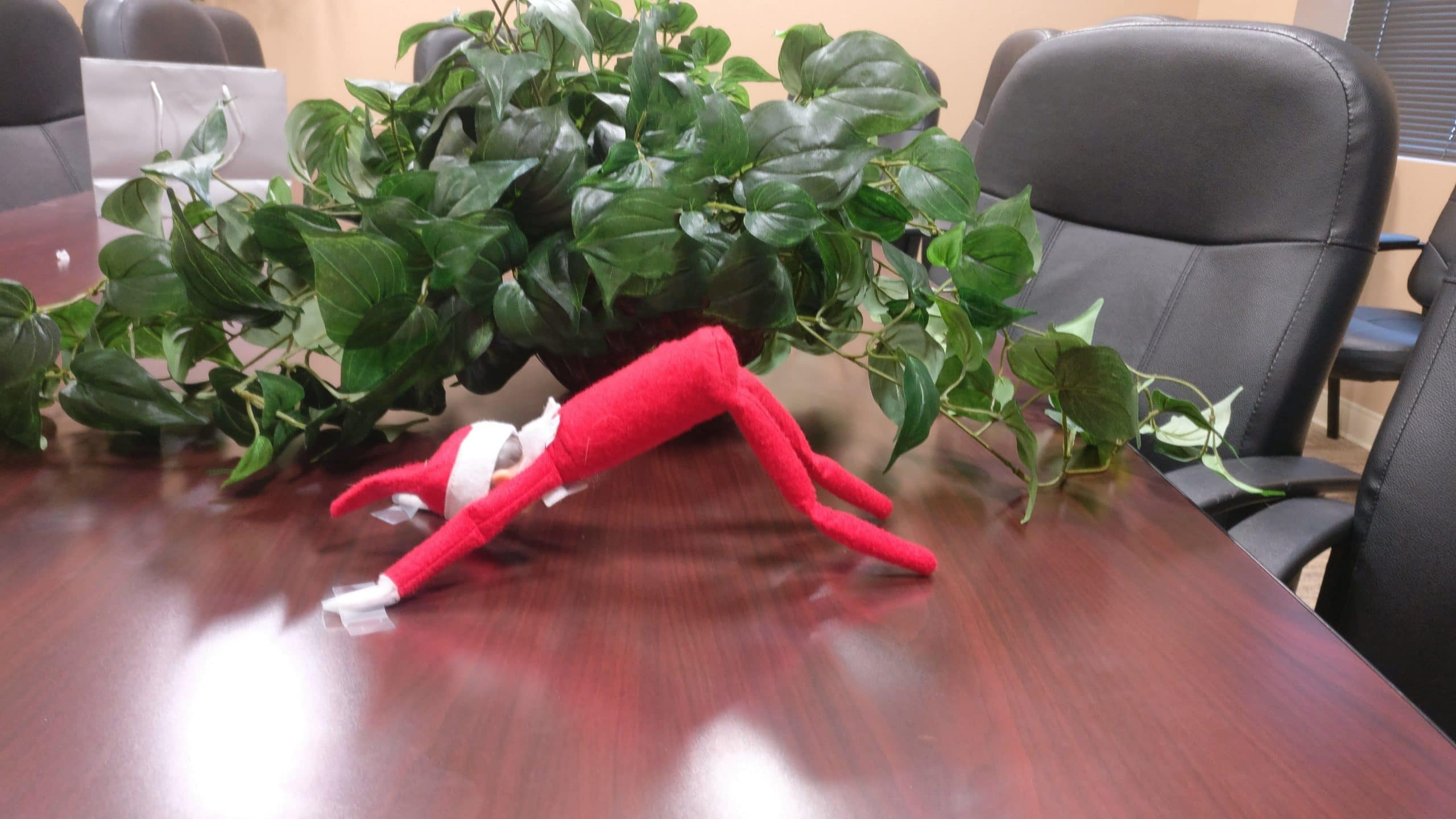 Elf on the shelf doing a downward dog pose.