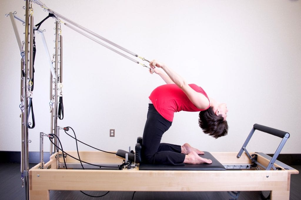 Women doing posture exercises in specialized physical therapy equipment.
